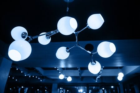 A beautiful modern chandelier in blue hangs on the ceiling. The main color of the Year 2020. Фото со стока