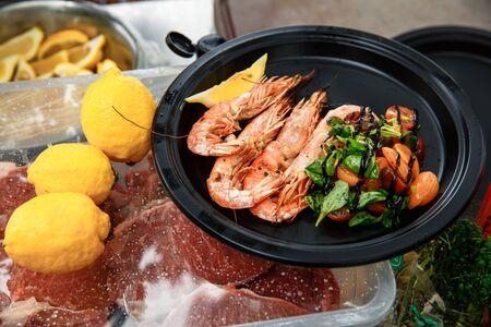 Large, fresh shrimp, grilled. Langoustines lie in a black, round plate with salad. Banque d'images