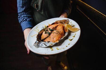 Juicy baked fish steak lies on a round plate. Stock fotó