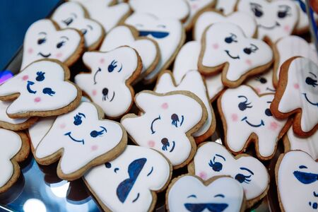 Many different cookies in the form of teeth lie in a rectangular plate .