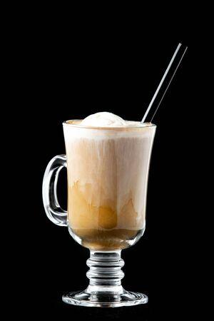 Koffie met ijs in een glas. In het glas zit een buis om een drankje van zwarte kleur te drinken. Geïsoleerd op zwarte achtergrond.