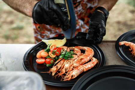 The waiter pours the sauce with large fresh shrimps, which are grilled. Langoustines lie in a black round plate with vegetables.