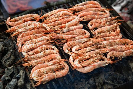 Cooking large and fresh shrimp on the grill, which lies on the coals. Langoustines lying on the grill. Banque d'images