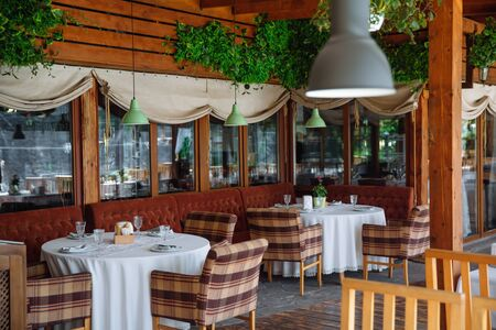 The cozy interior of the restaurant.There are soft sofas with tables and upholstered chairs. Foto de archivo
