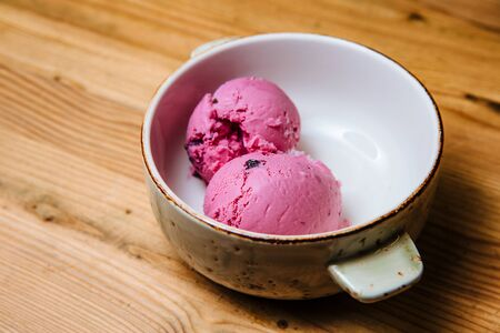 Two balls of pink ice cream in a bowl on a wooden table.
