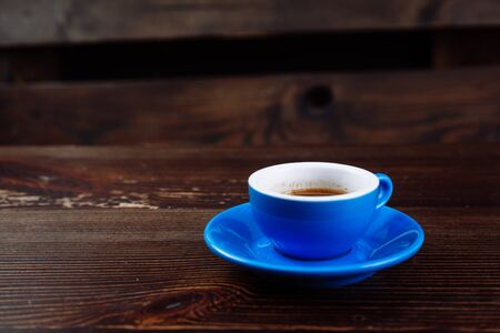 Schmutzige blaue Tasse nach dem Kaffee auf einem Holztisch. Standard-Bild
