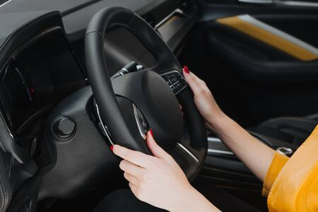 Female hands on the steering wheel of a car while driving.