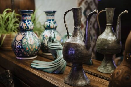An ancient copper decanter and an ornate clay jug stand on a shelf.