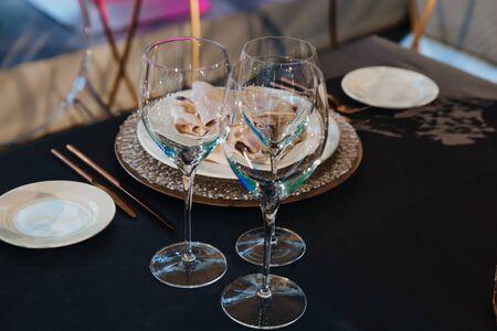 Glasses, forks, knives, plates on a table in restaurant served for dinner.