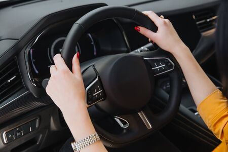 Womans hand on the steering wheel.