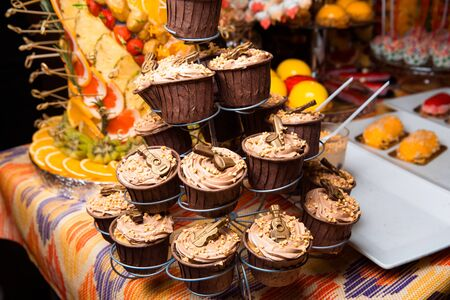 Freshly made cupcakes stand on a stand.