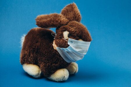 Toy bunny stands in a medical mask on a blue background. Concept of protection from respiratory disease, virus. Stop coronavirus.