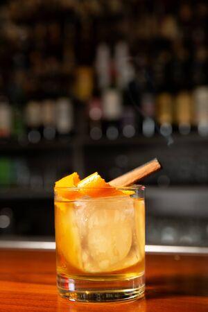 Orange cocktail with ice cube and orange zest. Stock Photo
