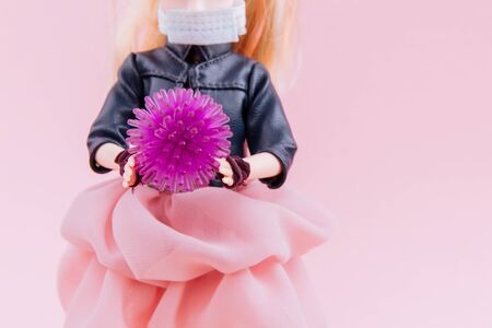 The doll, in a protective mask, is holding abstract virus strain model coronavirus covid-19 on pink background. Virus Pandemic Protection Concept. Banque d'images