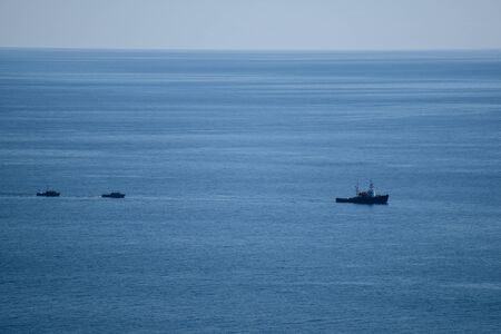 A large sea ship is sailing, and two small ships are sailing behind it, in a calm blue sea.