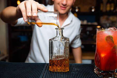 The barman pours whiskey into a transparent decanter.