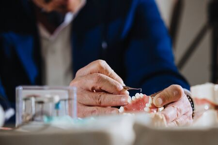 A dental technician processes a cast from the jaw of the patient. Standard-Bild