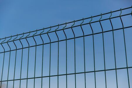 Steel grill fence with wire against the blue sky.