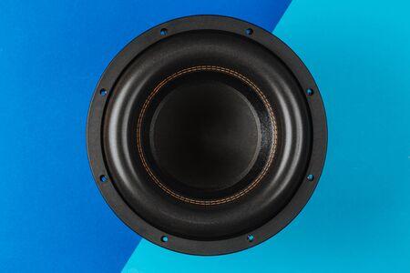 Car audio, big black subwoofer on a blue-light blue background. Close up. Banque d'images