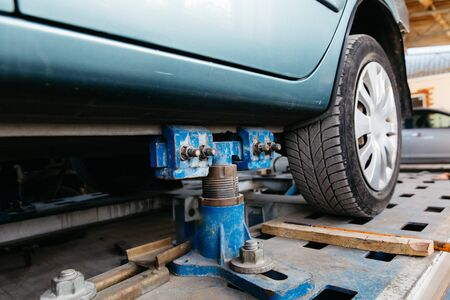 A blue car is lifted on a lift for repair in a car service center.