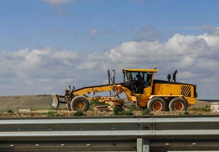 Grader yellow, industrial machine for the construction of new roads.
