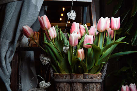A bouquet of gently pink tulips in a wooden box.