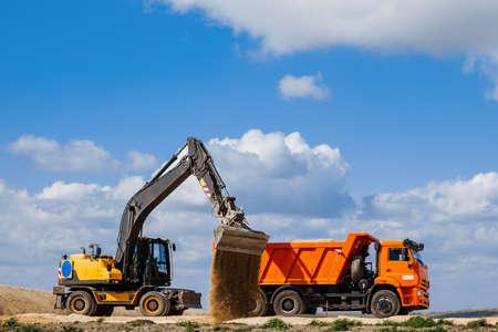A yellow backhoe loader loads the earth into a truck Reklamní fotografie