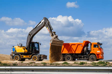 A yellow backhoe loader loads the earth into a truck during the construction of a road against a blue sky with clouds. Imagens