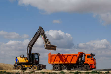 A yellow background loader loads the earth into a truck during the construction of a road against a blue sky with clouds.