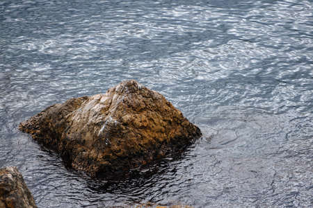 A picturesque lonely large stone stands on all sides surrounded by water. Sea landscape.