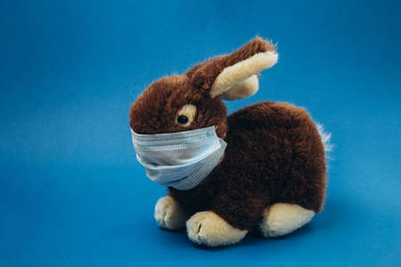 Toy bunny stands in a medical mask on a blue background. Concept of protection from respiratory disease, virus, and individual respiratory protection. Stop coronavirus. Stockfoto