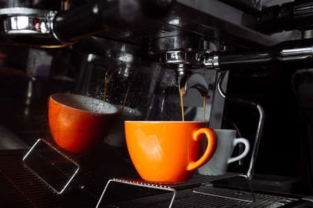 Coffee is poured into two cups from a coffee machine.