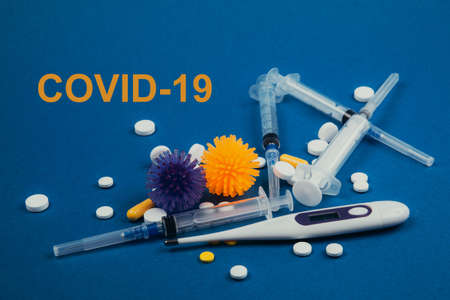 Thermometer, syringes, abstract virus model and pills on a blue background. Covid-19 written. Virus pandemic protection concept.