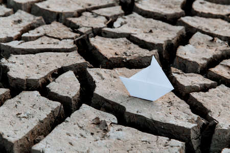 White paper boat on dry, dry soil with cracks. Global warming concept