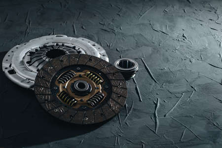 Automotive clutch mechanism, disc, basket and bearing for auto on a black background.