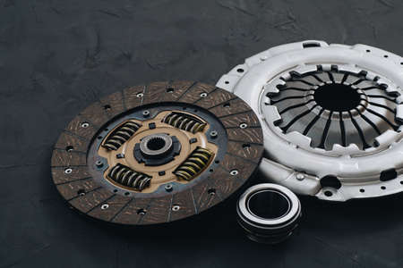 Automotive clutch mechanism, disc, basket and bearing for auto on a black background. Car parts. Close up Archivio Fotografico
