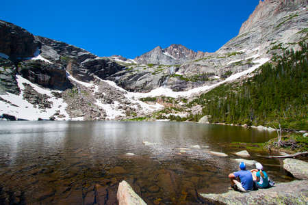 Happy couple in front of a mountain with a glacier in summer, Black Lake, Rocky Mountains National Park, USA photo