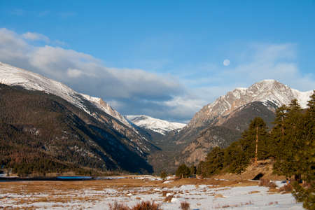 view of Rocky Mountains in early morning with a moon on a cloudy sky Stok Fotoğraf