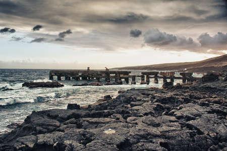 ship wreck: old bridge rack on an ocean lava beach in Hawaii during sunset