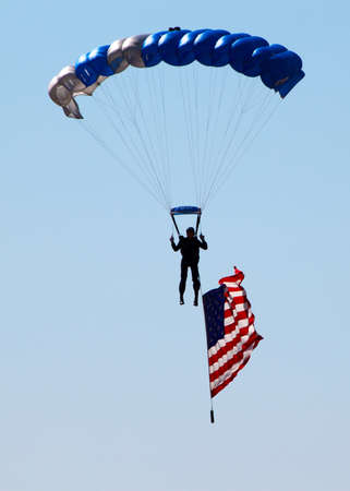 silhouette of skydiver with USA flag photo
