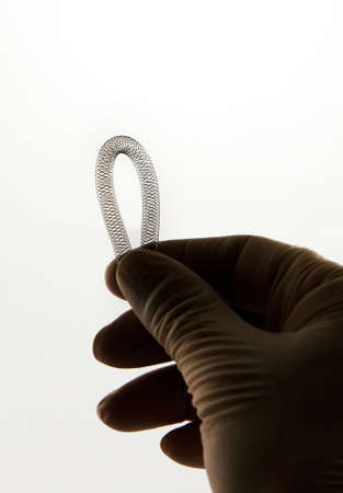 nitinol: surgeons hand holding self-expanding braided nitinol stent for endovascular surgery Stock Photo