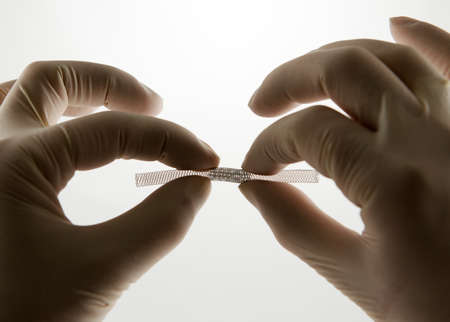 surgeon's hands compressing  self-expanding braided nitinol stent for endovascular surgery
