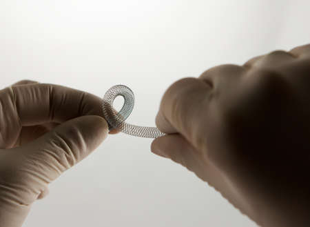 restenosis: surgeons hands twisting self-expanding braided nitinol stent for endovascular surgery