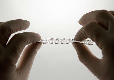 zatkanie: chirurga ręce ciągną własny rozszerzający oczkach stentu nitinolu dla zabiegu wewnątrznaczyniowego