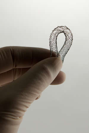 nitinol: surgeons hand holding self-expanding meshed nitinol stent for endovascular surgery