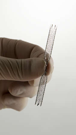 surgeon's hand compressing self-expanding meshed nitinol stent for endovascular surgery Stockfoto