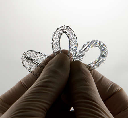 nitinol: surgeons hand holding self-expanding nitinol stents for endovascular surgery for comparison Stock Photo