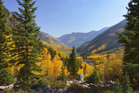 golden and green aspen overlooking Maroon Lake and Elk Mountains in Colorado during fall Stock Photo