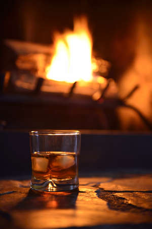 glass of hard liquor with ice cubes in front of the fireplace at night Stock Photo