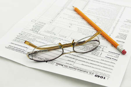 preparation of Internal Revenue Service form 1040 for income report and US tax return Stock Photo - 17111099